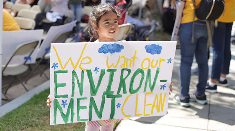 """A small child holds a sign up at a protest against oil drilling in neighborhoods that reads """"We want our ENVIRONMENT CLEAN."""""""